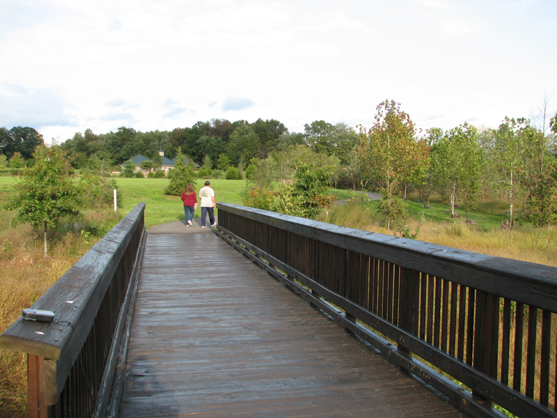 People walking past bridge on path in Northern Fauquier Community Park